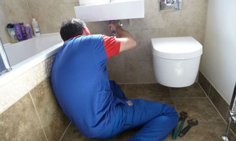 A plumber fixes a bathroom sink